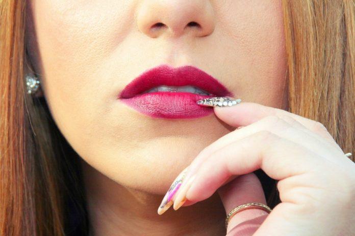 Kobieta zastanawiająca się jak zlikwidować pękające paznokcie