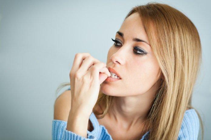 Kobieta zastanawia się jak przestać obgryzać paznokcie